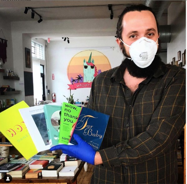 Bookseller Nathan McDowell wears a mask while showing off a few of his favorite indie press reads at Two Dollar Radio Headquarters in Columbus, Ohio, the bookstore division of indie press Two Dollar Radio.